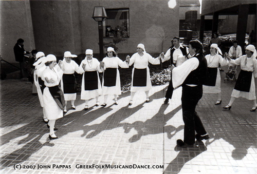San Joaquin Delta College Hellenic Dancers doing the Greek Syrtos dance at the school's new campus dedication in 1977.  They wear the traditional Greek folk dance costume.  A musician is playing a Thracian gaida in the center of the circle.  Used by permission.