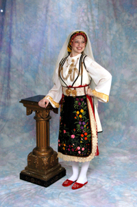 "Women's Festive Costume.  ""This is a festive costume made of a variety of materials and a wealth of jewelry. It is made up of a sleeveless cotton tunic with a multi colored embroidered hem, a silk jabot-trachilia, pure silk sleeves with lace. The white woolen coat known assigouna has black twisted silks at each seam and back. The headgear with coins and ornaments called beramia is covered with a white silk shawl called botia. The apron is of velvet with floral embroidery."" (http://www.greekfolkdancers.com/costumes.htm)"