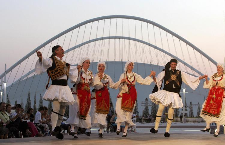 A Greek folk-dance group performs the horo in front of the Olympic Velodrome at the Olympic Complex in Athens during the Games of 2005. (Louisa Gouliamaki/AFP/Getty Images)